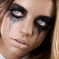 woman with dark gothic eye makeup and very long false eyelashes