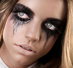 woman with dark gothic eye makeup and very long false eyelashes